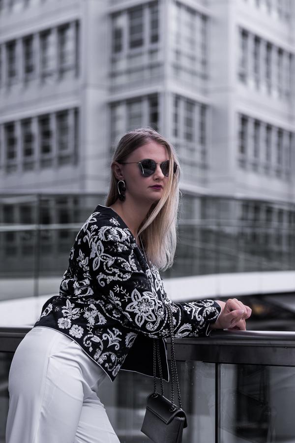 Fashion Week 2017 / Fashion Week 2018 Mit diesen 10 ultimativen Tipps kommst du ganz einfach auf die Fashion Week und zum Runway in New York, Paris oder Berlin. Klicke hier für exklusive Fashion Week Tipps. Street Style: Be Sassique trägt hier eine weiße Schlaghose, eine Barock Jacke mit Stickereien, Mismatched Ohrringe und eine Metallic Tasche