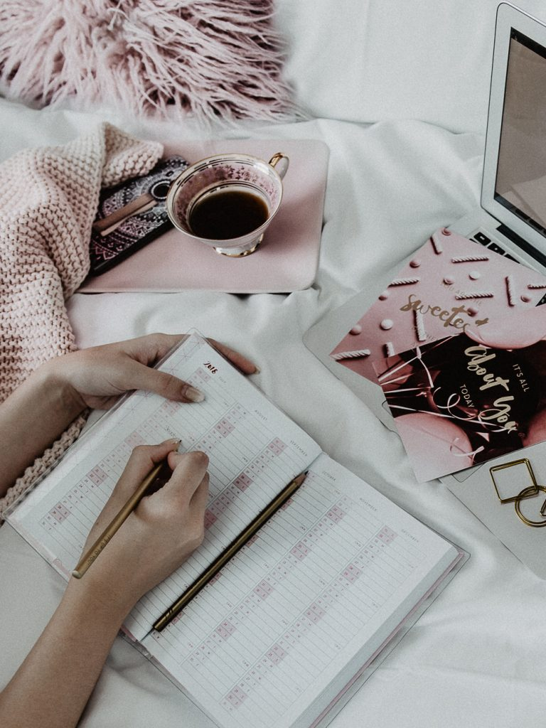 Pink and White Bed Flatlay for Instagram in minimal chic- Blonde Girl is writing in a calendar doing a coffee break by Be Sassique