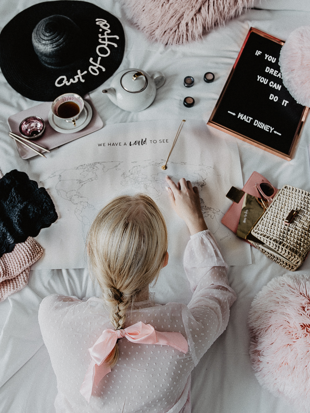 Pink and White Bed Flatlay for Travelinspo at Instagram in minimal chic- Blonde Girl lying in bed is looking at a map for the next vacation destination and all her travel dreams by Be Sassique